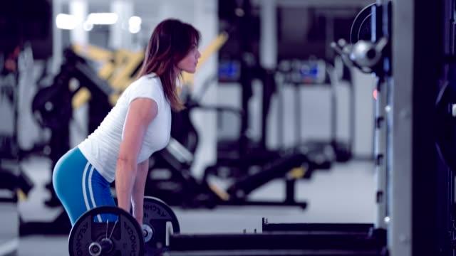 Mujer-culturista-realiza-peso-muerto-Mujer-hermosa-haciendo-peso-muerto-en-gimnasio