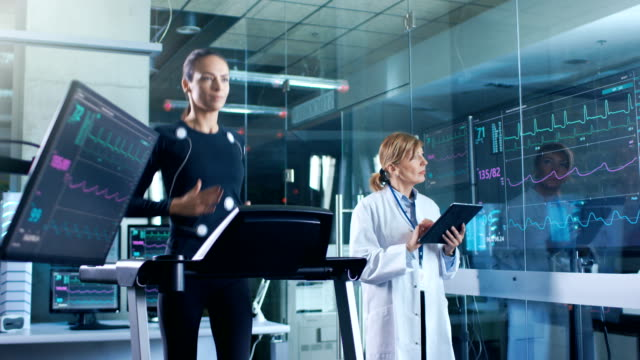 Woman-Athlete-Runs-on-a-Treadmill-with-Electrodes-Attached-to-Her-Body-while-Scientist-Holding-Tablet-Computer-Supervises-whole-Process-In-the-Background-Laboratory-with-Monitors-Showing-EKG-Readings-