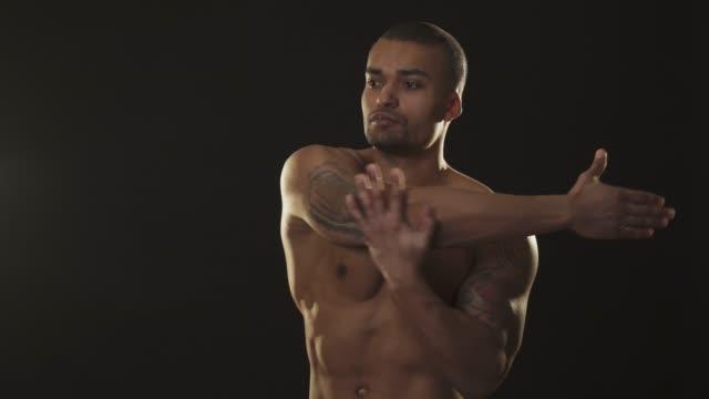 Atheltic-shirtless-handsome-African-man-warming-up