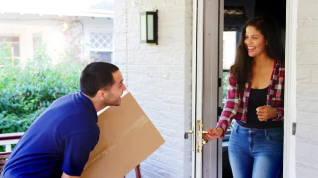 Mensajero-entrega-el-paquete-a-la-mujer-en-casa
