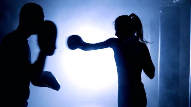 Silhouettes-of-a-female-boxer-punching-a-boxing-bag-with-boxing-gloves-in-a-smoky-gym