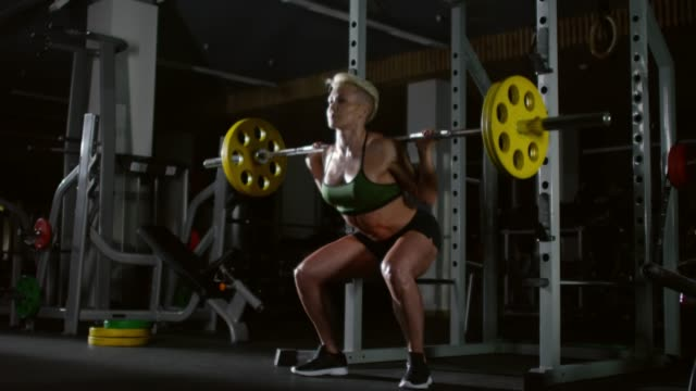 Muscular-Woman-Doing-Weighted-Squats