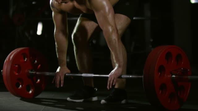 Deportista-haciendo-ejercicio-de-peso-muerto-con-barra-en-gimnasio-oscuro