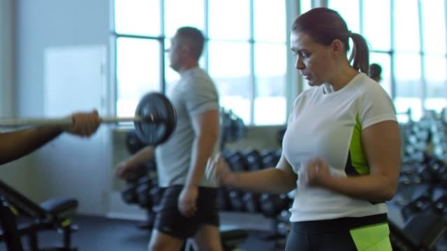 Mujer-a-hombre-haciendo-barra-rizos-en-gimnasio