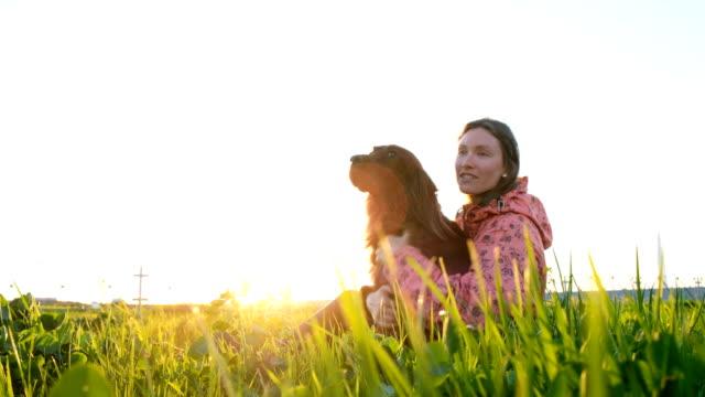 Mujer-jugando-con-el-perro-al-atardecer-niña-con-mascota-sentados-sobre-la-hierba-y-relajante-en-la-naturaleza
