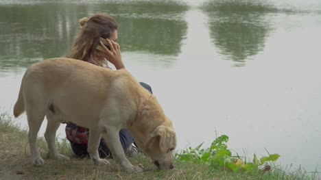 Curly-woman-and-labrador-is-resting-near-the-river