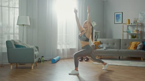 Beautiful-Confident-Busty-Fitness-Girl-in-an-Athletic-Top-is-Doing-Stretching-Yoga-Exercises-in-Her-Bright-and-Spacious-Apartment-with-Minimalistic-Interior-