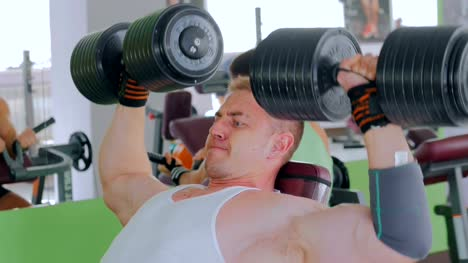 Athletic-young-man-lifting-dumbbells-at-gym