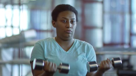 Woman-with-Dumbbells-Doing-Bicep-Curls-before-Mirror