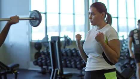 Woman-Helping-Man-Doing-Barbell-Curls-in-Gym