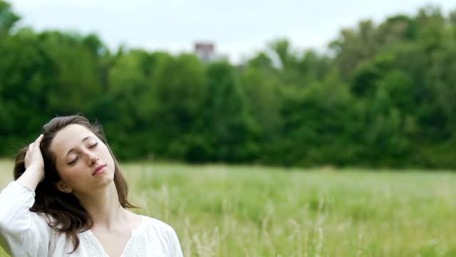 Mujer-profundamente-relajada-en-campo-verde-toca-su-cabello-con-ojos-cerrados-unidad