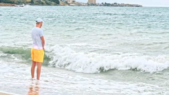 Junge-allein-Blick-auf-den-Horizont-in-Strandnähe-bei-Sturm-