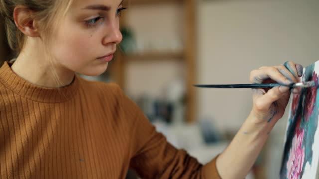 Pintor-joven-encantador-es-que-representa-flores-sobre-tela-con-pincel-en-mano-sucia-y-mirando-el-cuadro-concentrado-en-el-trabajo-Concepto-visual-de-la-artes-y-de-la-juventud-