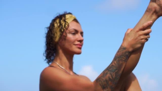 Ein-junges-Mädchen-in-einem-Bikini,-balancieren-auf-einem-Stein-sitzend-und-Übungen-für-die-Bauchmuskeln,-Beine-abwechselnd-anheben.-Training-auf-dem-Hintergrund-des-Ozeans-auf-den-schwarzen-Sandstrand