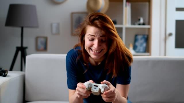 Chica-decidida-jugando-un-videojuego-en-casa-Mujer-jugadora-excitada-sentada-en-un-sofá-jugando-y-perdiendo-en-videojuegos-en-una-consola-usando-un-mando-inalámbrico-Habitación-acogedora-ambiente-casero-encantador