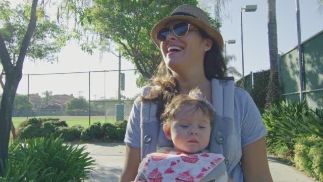 Frau-mit-einem-Baby-in-Träger-lächelnd-wie-sie-in-einem-Park-geht