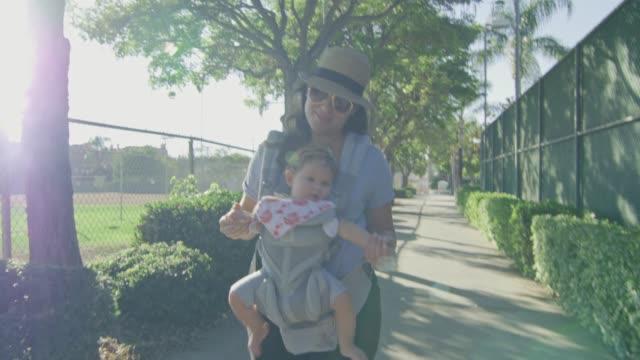 Frau-lächelnd-wie-sie-mit-Baby-in-Träger-in-einem-Park-geht