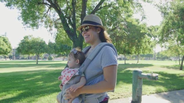 Glückliche-Frau-zu-Fuß-auf-einem-Park-trägt-ihr-Baby-auf-Träger