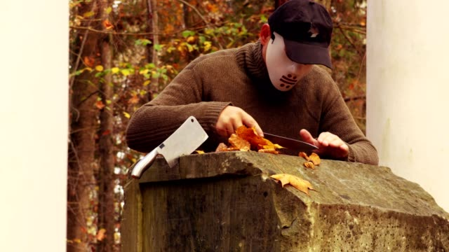 Man-with-scary-Halloween-mask-sharpening-knives-in-park
