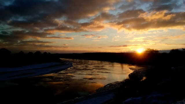 Winter-landscape-with-moving-ice-floes-and-clouds-at-sunset-timelapse-4K