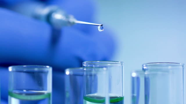 Auxiliar-de-laboratorio-realizando-experimentos-cuidadosamente-mezclar-reactivos-de-diferentes