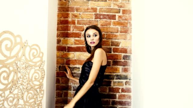 Demonstration-einer-neuen-Kollektion-von-Kleidung-auffällig-Brünette-mit-dunklem-Make-up-im-Abendkleid-auf-einer-Schulter-posiert-für-Foto-Shooting-auf-Hintergrund-der-Ziegelmauer