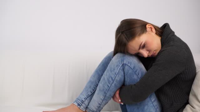 Mujer-triste-destacó-sentado-en-el-sofá-en-casa-4K