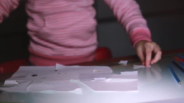 Primer-plano-de-niña-las-manos-en-forma-de-hoja-de-papel-de-corte-de-suéter-rosa-con-tijeras-sobre-una-mesa-de-vidrio