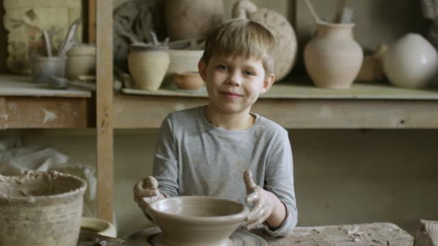 Boy-Posing-in-Pottery-Workshop