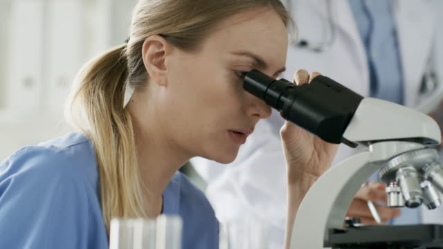 Woman-Using-Microscope-and-Talking-to-Colleague