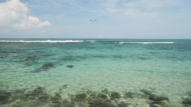 Airplane-landing-on-island-Bali-airport-under-blue-sea-with-waves-on-the-horizon
