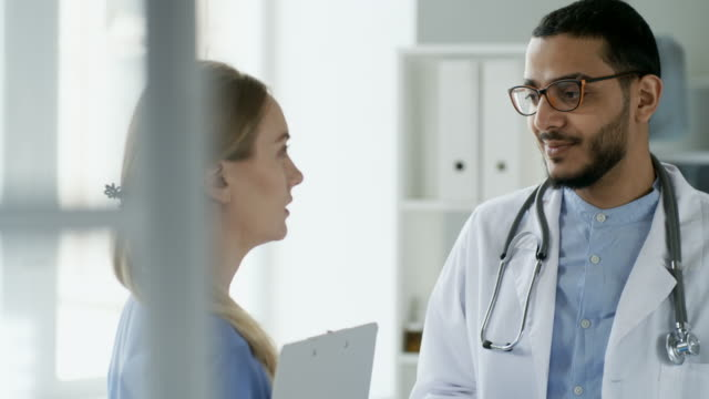 Multiethnic-Doctors-Talking-at-Work-in-Clinic