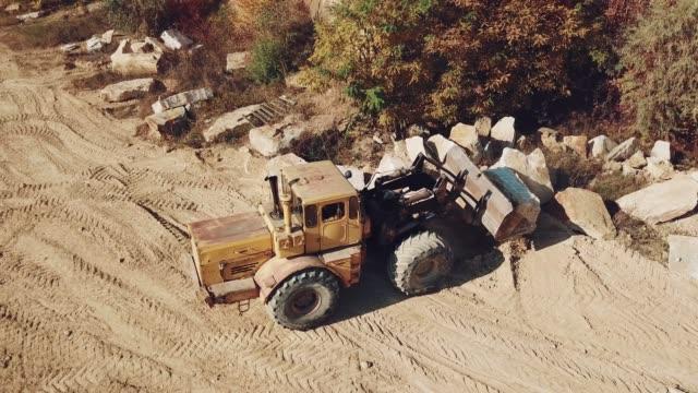 máquina-especialmente-equipada-con-un-id-de-cubo-trabaja-cerca-de-una-cantera-de-piedras-en-el-fondo-de-arena-