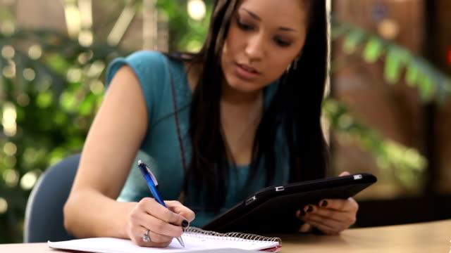 Una-linda-estudiante-toma-notas-mientras-estudia