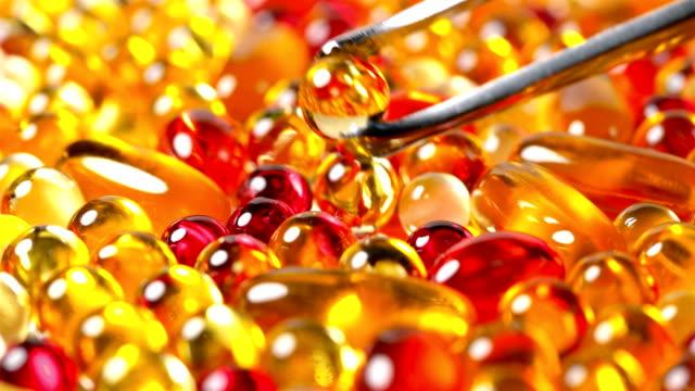 el-farmacéutico-toma-una-pastilla-o-vitamina-de-color-amarillo-con-las-pinzas-entre-su-gran-cantidad