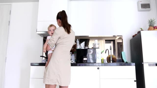 Mamá-con-el-bebé-sus-brazos-cocinando-cocina