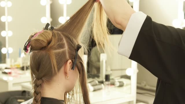 Hairstylist-combing-strand-hair-and-spraying-water-before-cutting-in-beauty-salon-Close-up-hairdresser-making-female-haircut-in-hairdressing-salon