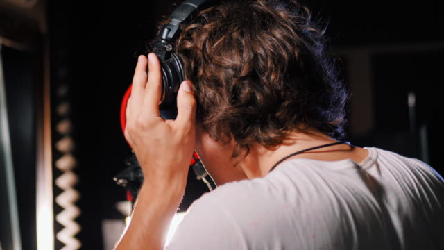 Young-handsome-singer-man-puts-on-headphones-in-the-studio-Recording-new-melody-or-album-Male-vocal-artist-with-curly-hair-preparing-for-working-4k