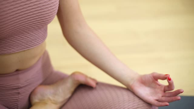 Joven-mujer-sentada-en-postura-de-loto-y-meditando-en-la-clase-de-fitness-con-espacio-libre-espacio-de-copia