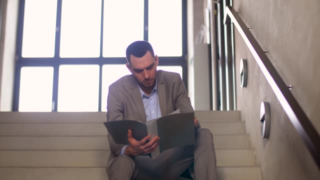 businessman-with-folder-sitting-on-stairs