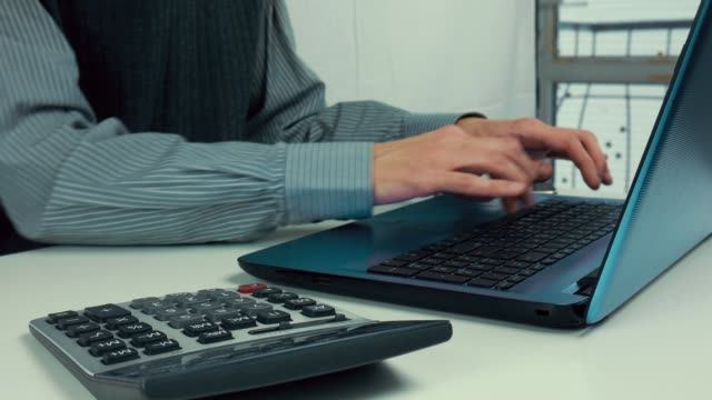 Male-hands-are-typing-text-on-a-laptop-White-table-calculator-office