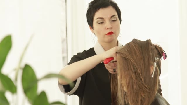 Haircutter-combing-female-hair-during-cutting-in-hairdressing-salon-Close-up-hairdresser-making-female-haircut-in-beauty-salon