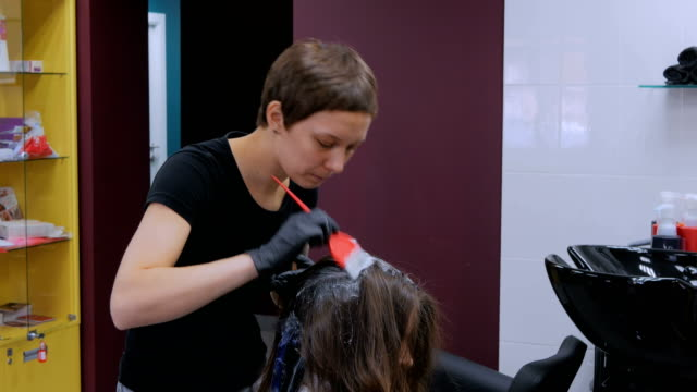 Professional-hairdresser-coloring-hair-of-woman-client-at-studio