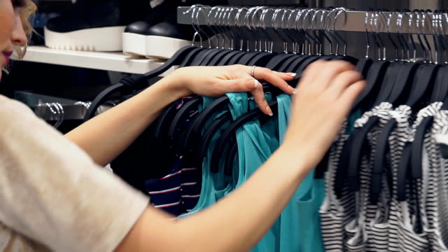 shopping-fashion-style-and-people-concept-Shopping-women-choosing-dress-in-mall-or-clothing-store-