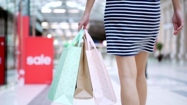 Geringen-Teil-unkenntlich-junge-Frau-im-gestreiften-Kleid-zu-Fuß-in-Richtung-Rolltreppe-mit-Einkaufstüten-in-der-Hand-nach-dem-erfolgreichen-Einkauf-am-Verkaufstag