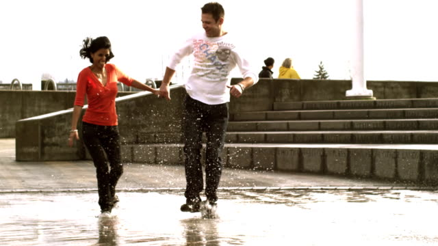 A-couple-runs-and-jumps-through-the-puddles-of-a-fountain-in-a-park