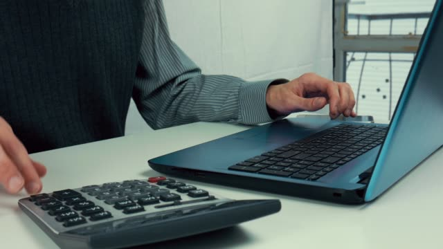 A-man-counts-finances-on-a-calculator-and-enters-information-into-a-laptop-Office-white-table-manager