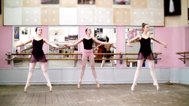 in-dancing-hall,-Young-ballerinas-in-black-leotards-perform-pas-echappe,-standing-on-toes-in-pointe-shoes-near-barre-at-mirror-in-ballet-class