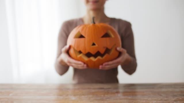 primer-plano-de-mujer-con-calabaza-de-halloween-en-casa