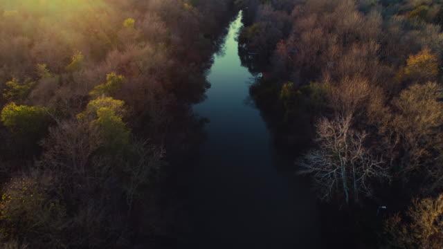 Luftbild-Drohne-Blick-über-den-Fluss-und-die-Herbst-Bäume-aus-dem-Wald-bei-Sonnenuntergang